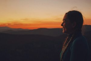 Photo of the author. Rachael has her long blonde hair in two braids. She is wearing a blue hiking shirt. She's standing on the top of a mountain, smiling into the sunset.